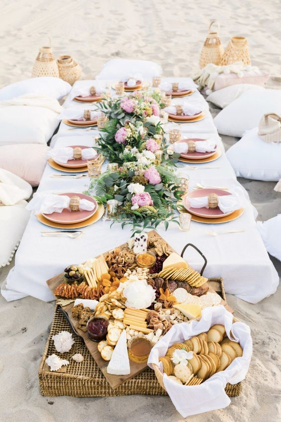 a pastel beach wedding picnic with a low table, pastel flowers and greenery, pastel plates and woven lanterns