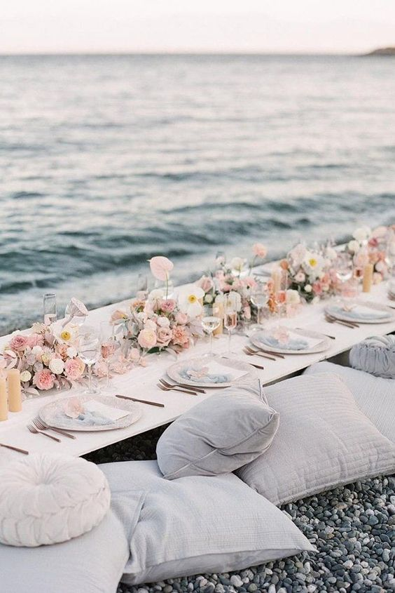 a pastel coastal wedding picnic table with pastel blooms, candles, neutral plates and lots of pillows