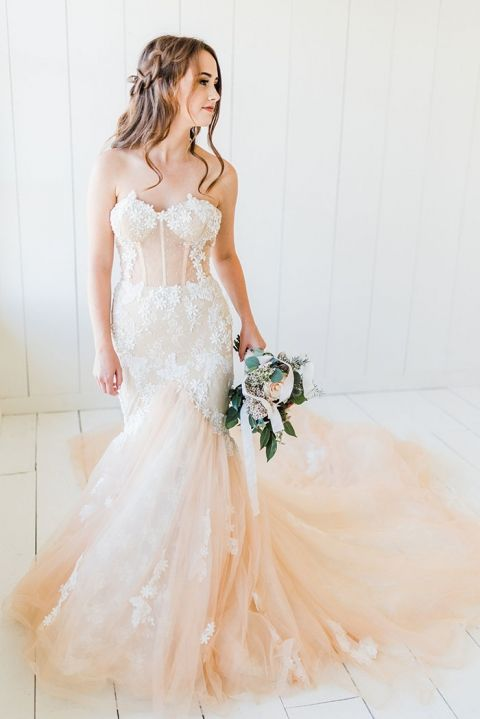 a pastel strapless mermaid wedding dress with white lace appliques, a train and a corset for a sexy and chic bridal look