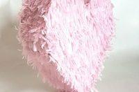 a pink fringe heart-shaped pinata is a very pretty and lovely idea with a touch of romance is a cool wedding guest book