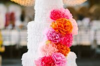 a pretty cake-shaped fringe pinata with colorful paper blooms is a gorgeous idea of an alternative wedding guest book
