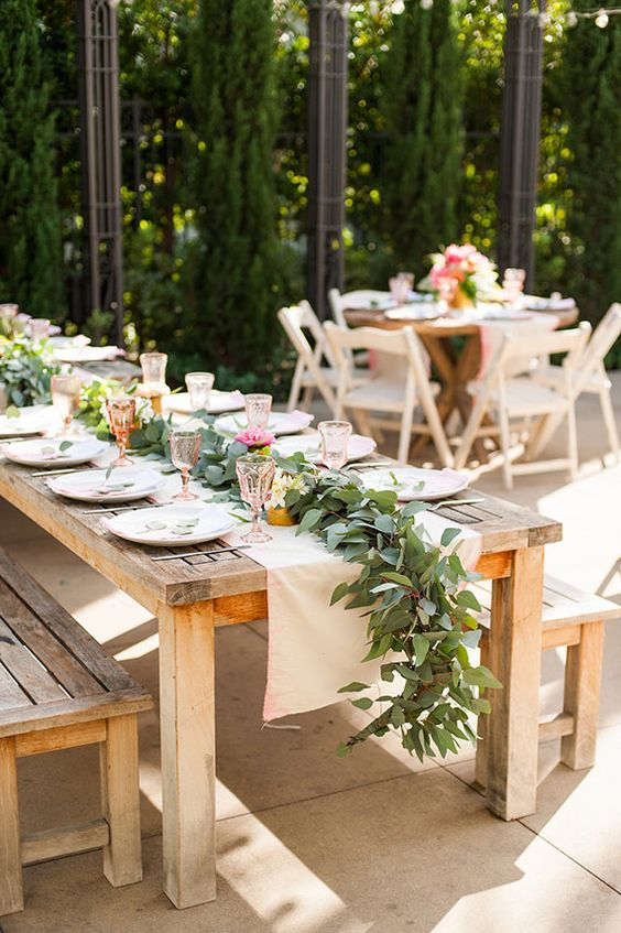 a pretty garden bridal shower with uncovered tables, a greenery and bloom runner, pink and amber glasses and white plates