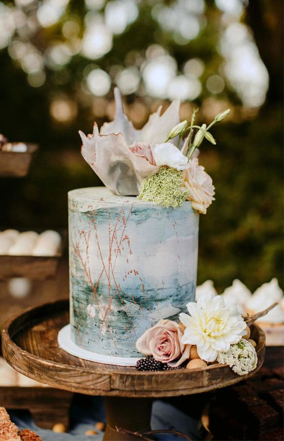 a pretty watercolor painted cake with seashells, pink blooms and greenery for a beach bridal shower