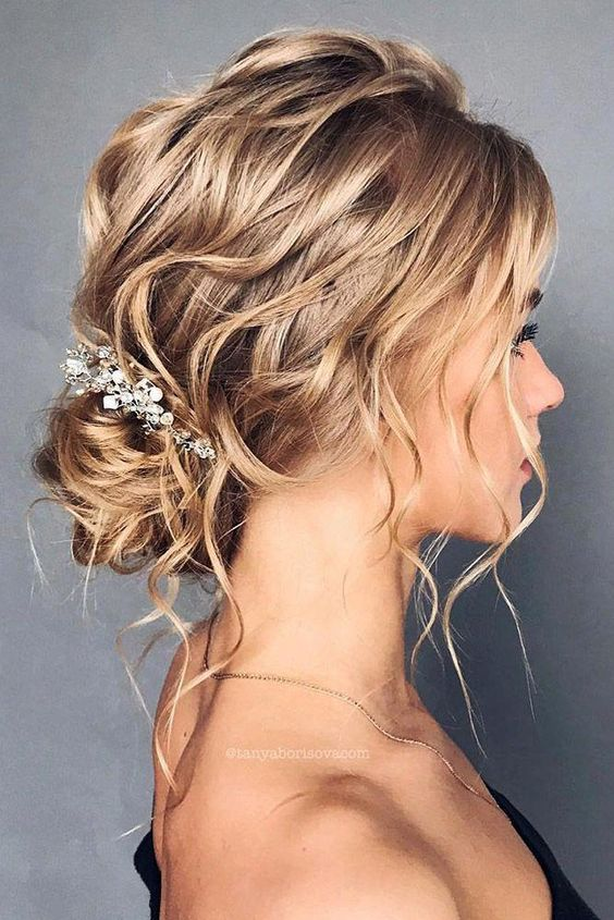 a refined and wavy messy low bun with a wavy top, locks down and an embellished hairpiece is a chic idea