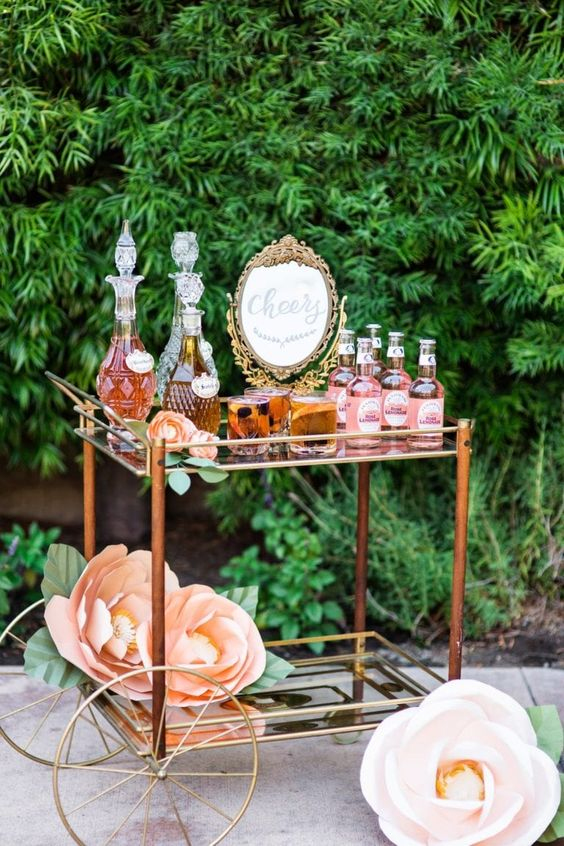 a refined bar cart with vines and soft drinks, a large vintage mirror in an exquisite gold frame, with large paper flowers