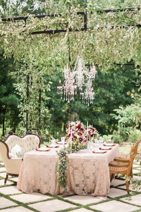 a refined garden bridal shower tablescape with a lace tablecloth, a greenery runner and bold blooms, crystal chandeliers and chic furniture