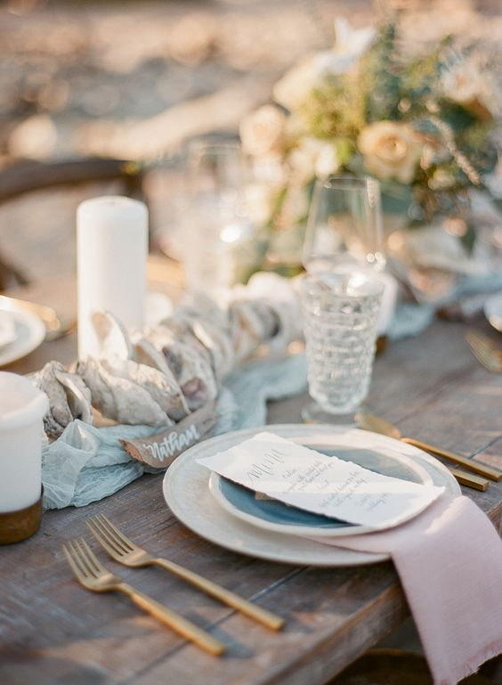 a romantic beach bridal shower table with seashell runners, candles, pink napkins, blue plates and gold cutlery