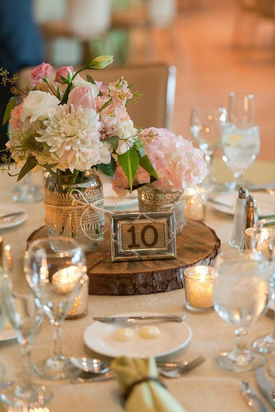 a rustic wedding centerpiece of a wood slice, a table number, pink and neutral blooms in jars wrapped with burlap