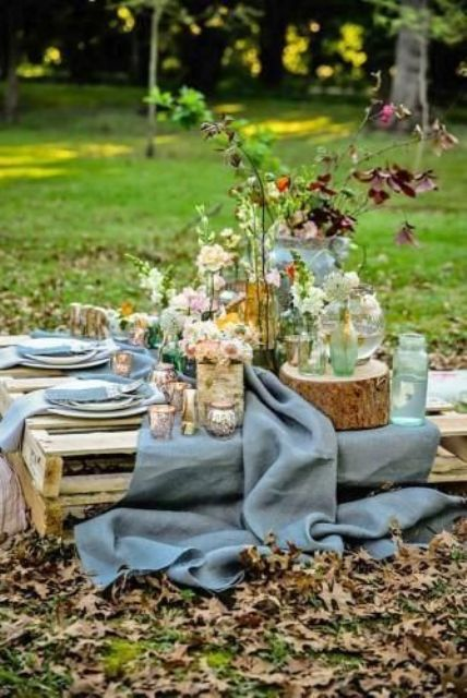 a rustic wedding picnic with a pallet table, a blue runner, pastel and neutral blooms, greenery, tree stumps and wood slices