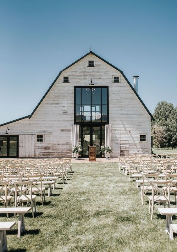 a serene outdoor barn wedding ceremony space with white benches and chairs, with white florals and curtains and no aisle decor