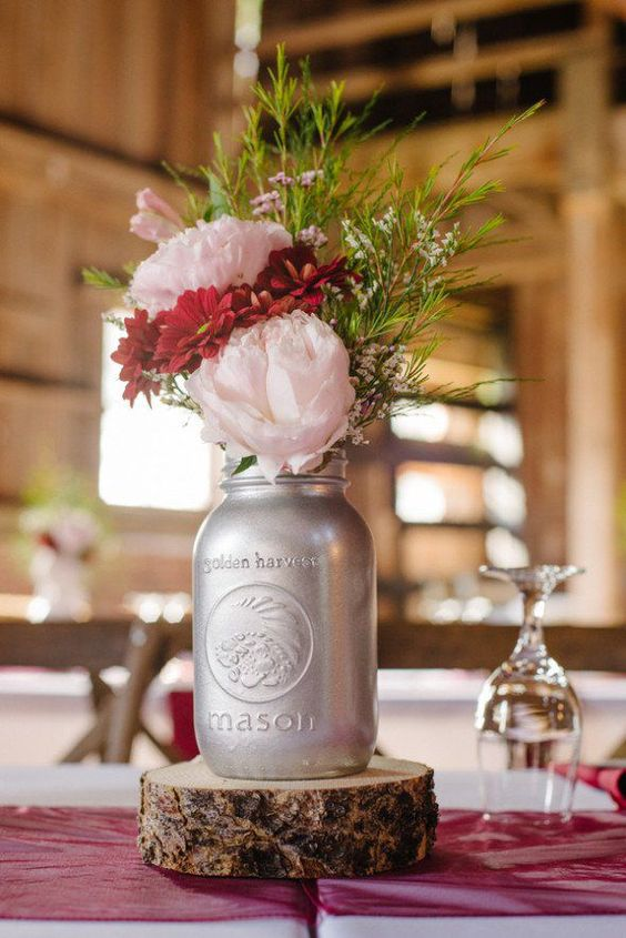 a simple and cute barn wedding centerpiece of a wood slice, a silver jar with greenery, pink and red blooms