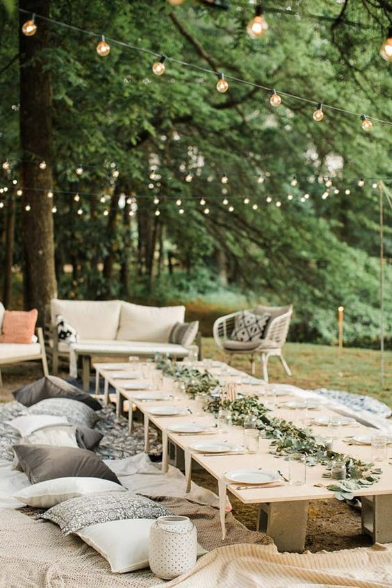 a simple and cute casual wedding picnic with a low table, printed blankets and pillows and a greenery runner plus candles