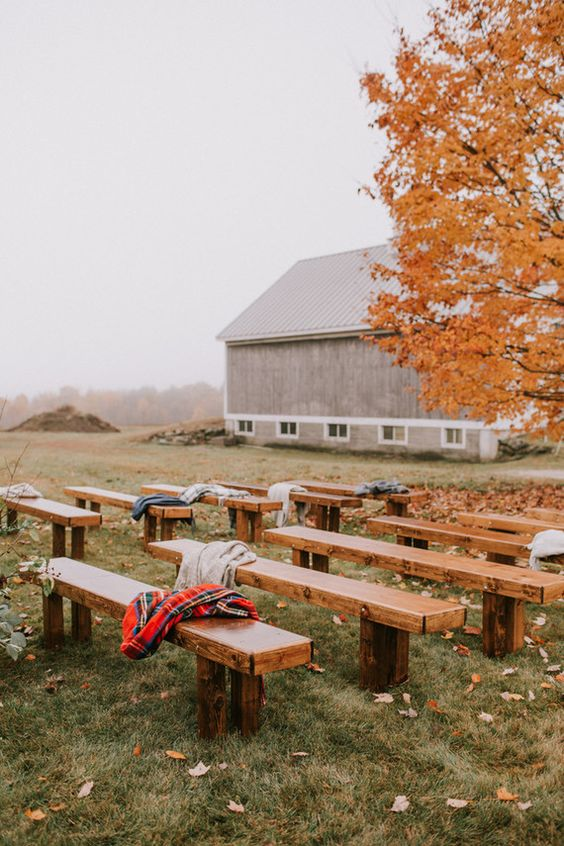 a simple and lovely outdoor barn wedding ceremony space with a large living tree, lots of fall leaves under it, wooden benches and bright blankets