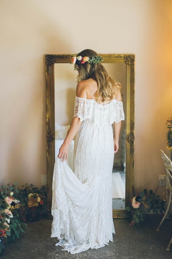 a simple boho lace off the shoulder wedding dress with a short train for a summer boho barn bride