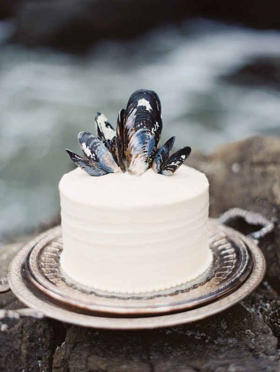 a simple white beach bridal shower cake with mussel shells on top is stylish and elegant