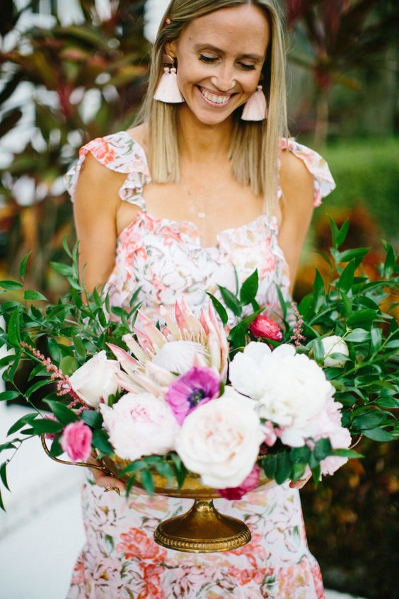 a statement flower centerpiece of blusha nd hot pink blooms and greenery for a boho garden bridal shower