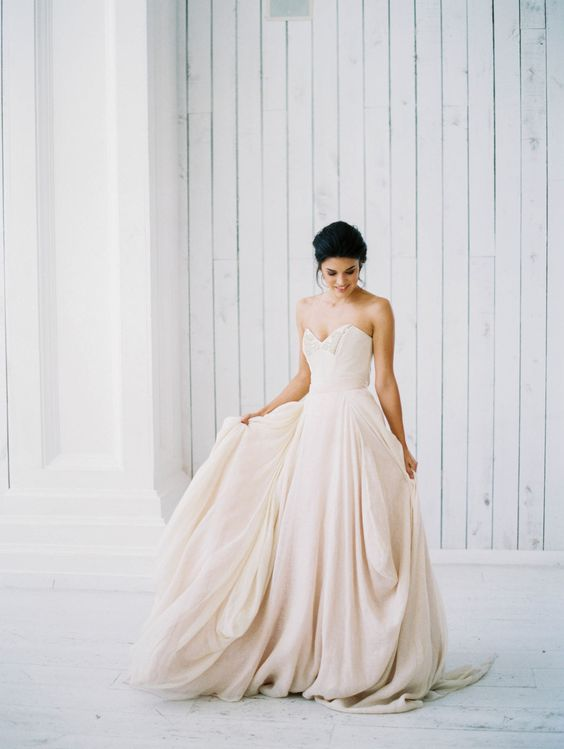 a strapless blush wedding ballgown with a draped and embellished bodice and a layered full skirt