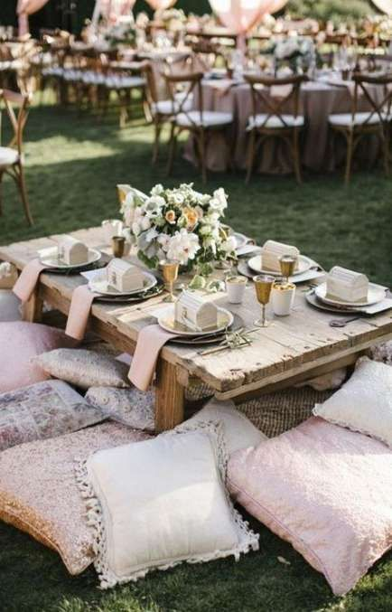 a stylish and refined wedding picnic with a low table, pillows, shiny chargers, neutral blooms and candles