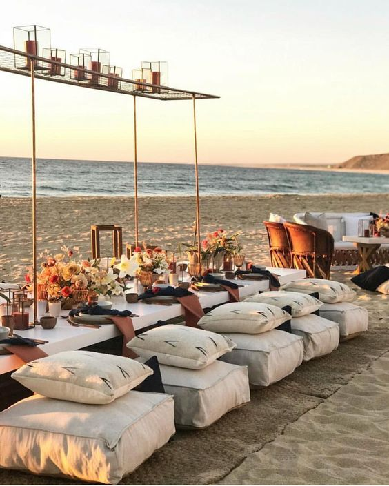 a stylish beach picnic bridal shower with white furniture and pillows, with dark linens, bold blooms and a lounge next to the table