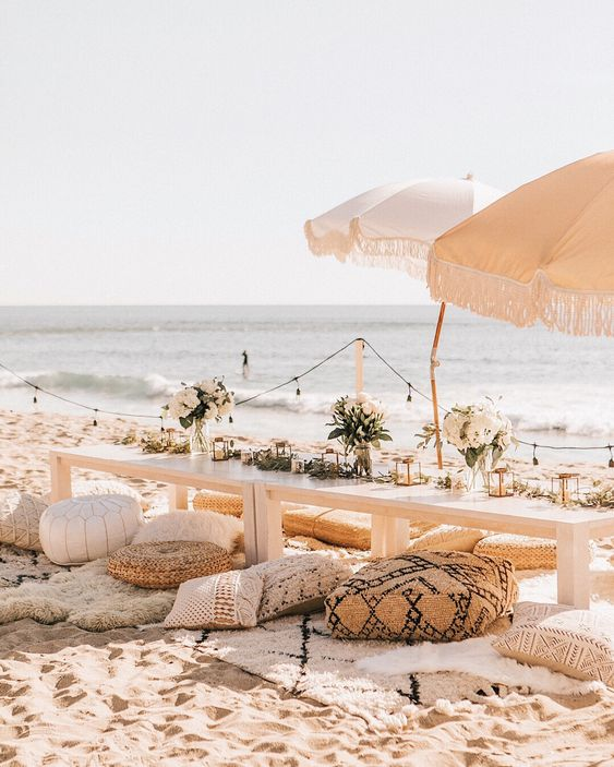 a stylish neutral beach bridal shower picnic with low tables, umbrellas, jute and leather ottomans, neutral blooms and candles