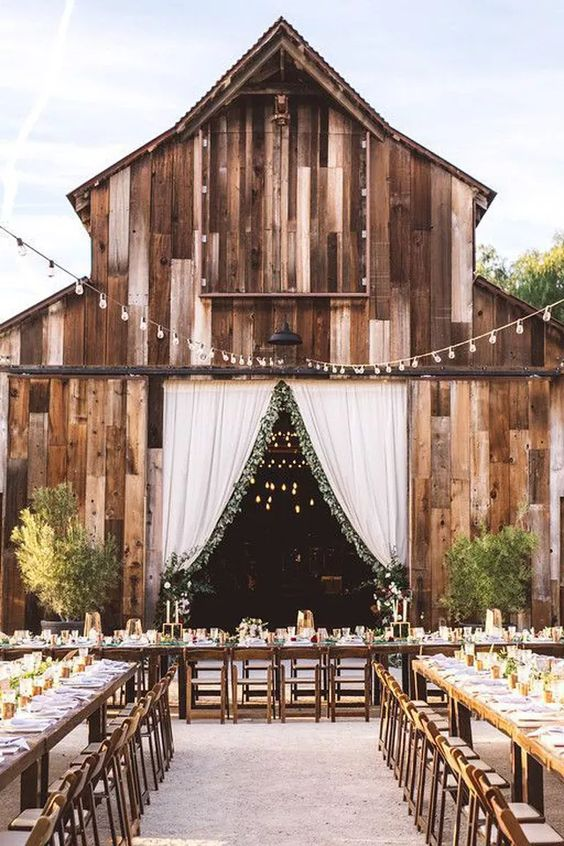 a stylish outdoor barn wedding reception with long tables, greenery arrangements, string lights and neutral linens is a chic idea