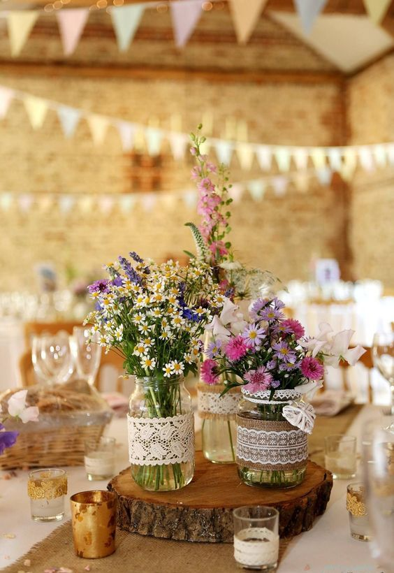 a summer barn wedding centerpiece of a wood slice, jars wrapped with burlap and lace and bright wildflowers plus candles