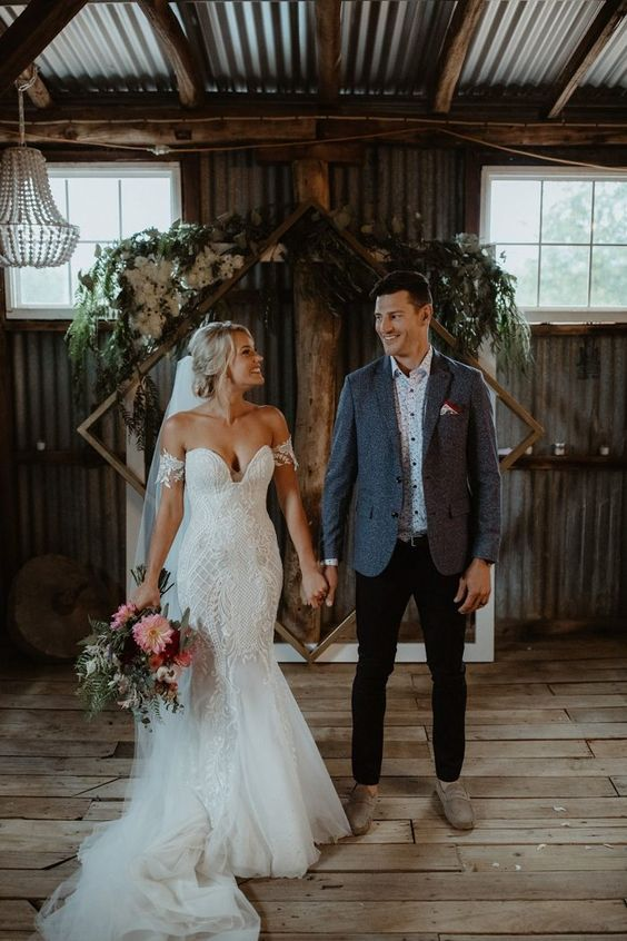 a super sexy off the shoulder boho lace mermaid wedding dress with a train and a veil is gorgeous