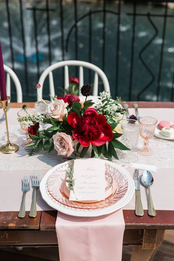 a vivacious garden bridal shower with blush and white linens, pink glasses and plates and a bold floral arrangement is chic
