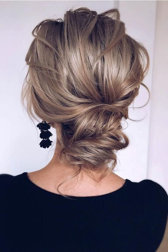 a wavy and chic low updo with a volume on top and some waves is a cool option for a modern refined bride