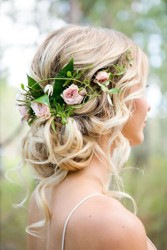 a wavy low updo with a volume on top and some waves down accented with greenery and pink roses is a lovely idea