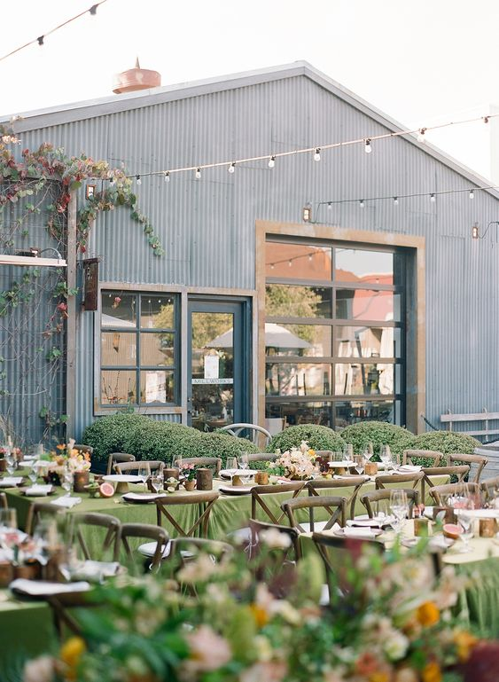a welcming outdoor barn reception space with long tables, stained chairs, green and white linens, bright florals and string lights over the space