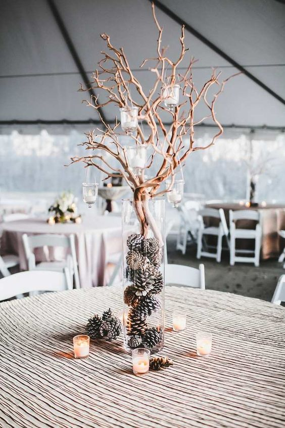 a winter barn wedding centerpiece of candles, a clear vase with pinecones and branches with candles hanging on them