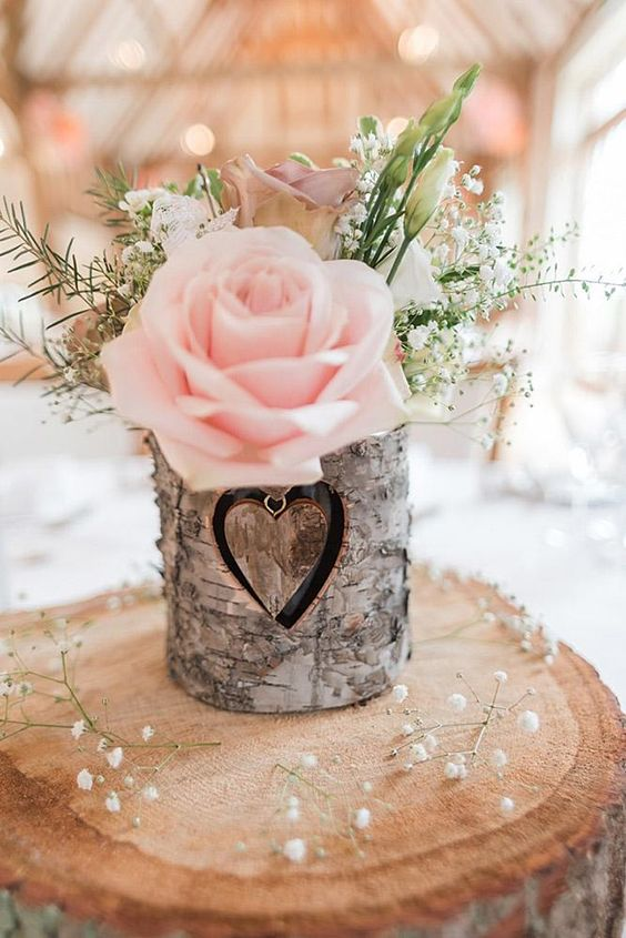 a wood slice with a bark wrapped vase, baby's breath, greenery and a pink rose is a great barn centerpiece
