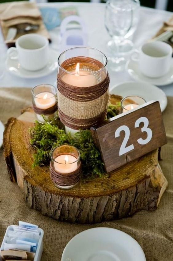 a wood slice with moss, candles wrapped with twine, a tall candle wrapped with twine and burlap and a table number