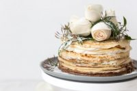 an adorable crepe wedding cake with cream cheese, white blooms, greenery and sugar powder is a lovely wedding dessert