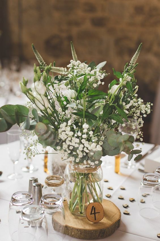 an airy barn wedding centerpiece of a wood slice, a wood slice table number and neutral blooms and greenery in a jar