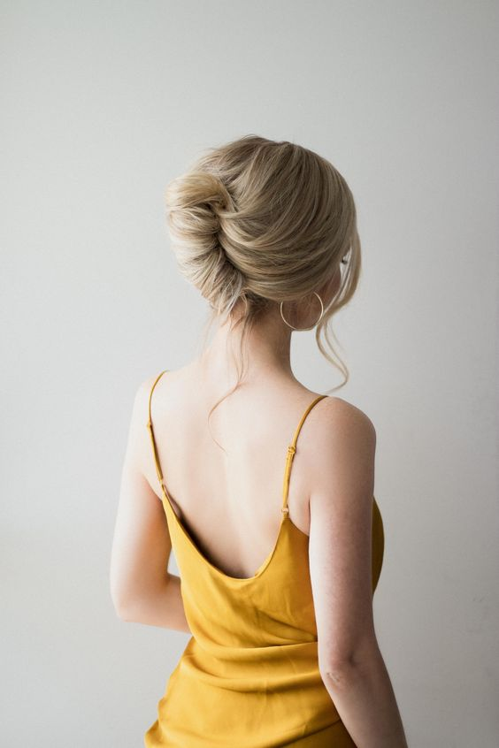 an elegant and chic low chignon with a volume on top and some waves down is classics that always works