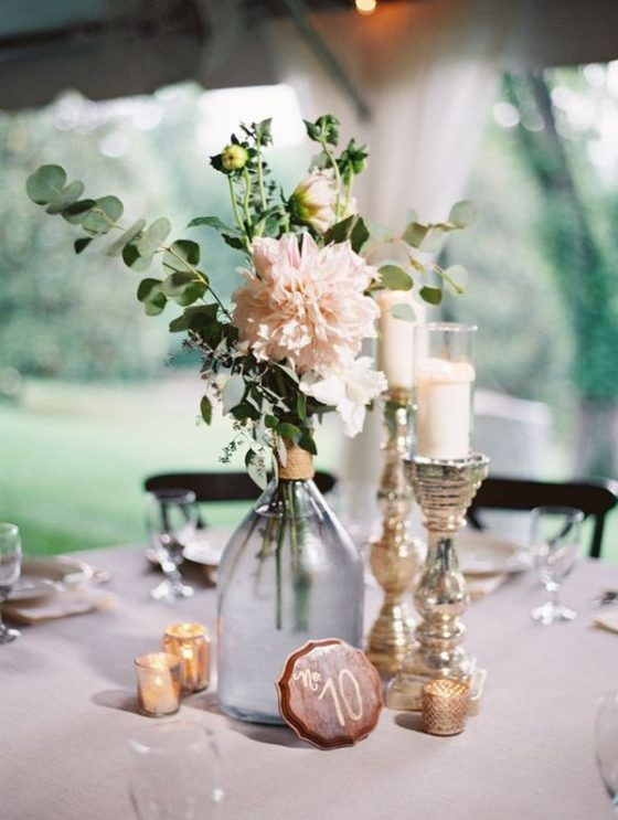 an elegant barn wedding centerpiece of metallic candleholders, a bottle with blush blooms and a mini table number