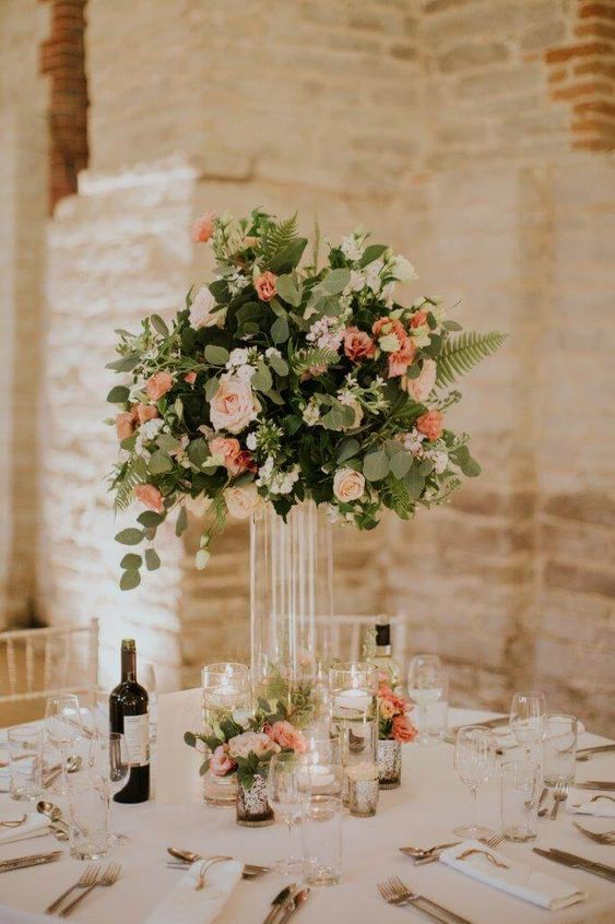 an elegant barn wedding centerpiece of peachy and blush blooms, greenery and floating candles in glasses