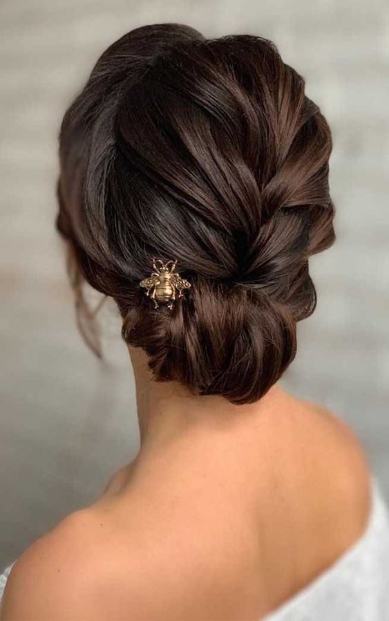 an elegant braided low updo with a twisted halo and a gold bug hairpiece is a very stylish and chic idea