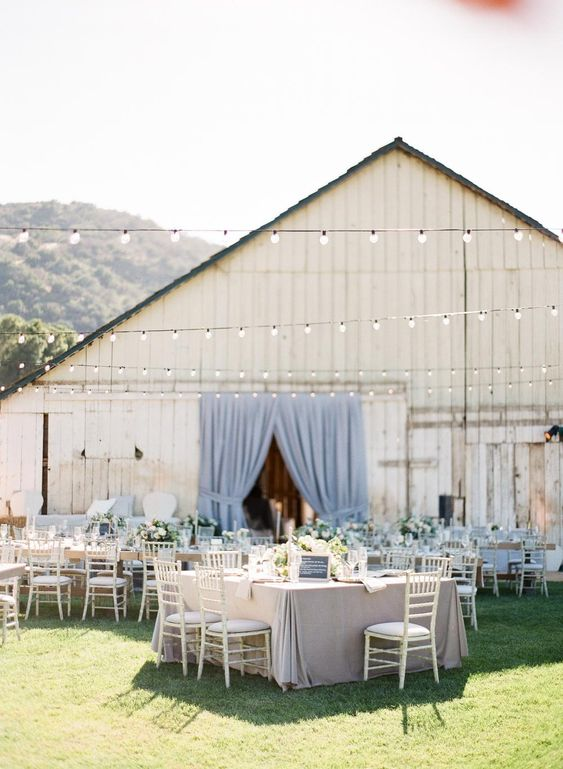 an elegant modern barn wedding reception with blue and grey linens and curtains, chic chairs and neutral florals is amazing