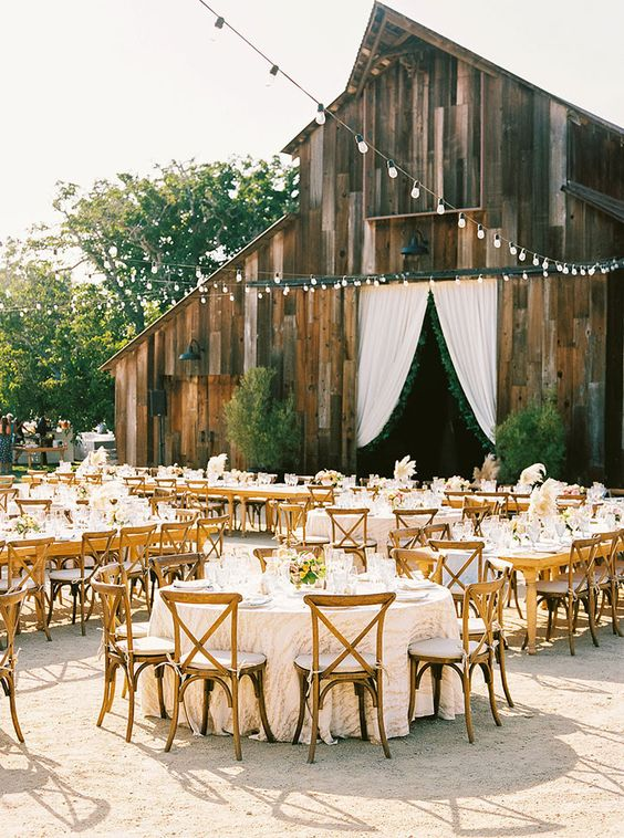 an elegant outdoor barn wedding reception space with round tables, pastel blooms and greenery, pampas grass and string lights over the space