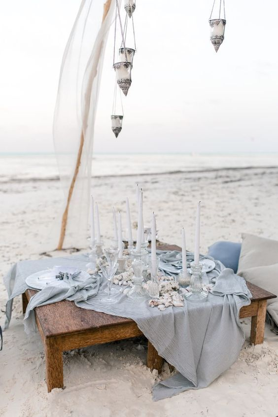 an ethereal light blue picnic setting with candle lanterns, a blue table runner, seasells and corals and white candles
