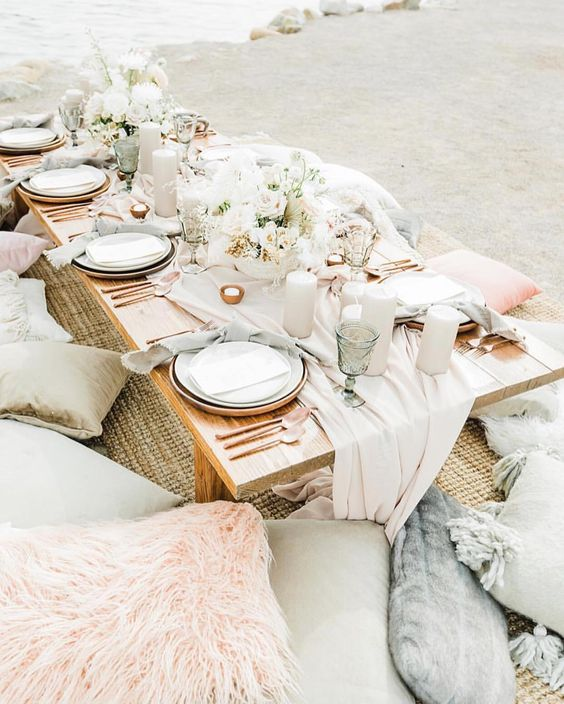 an ethereal pastel beach bridal picnic with pink and grey textiles, neutral candles and blooms and green glasses