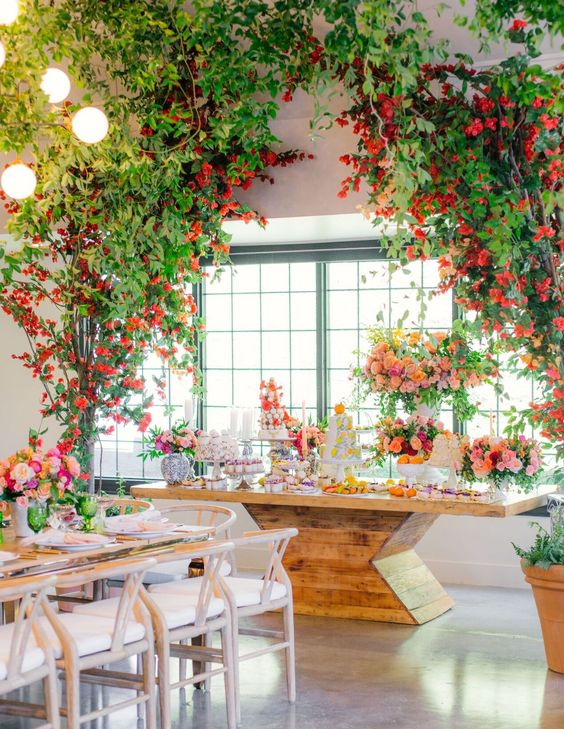 an indoor garden bridal shower space done with lots of greenery, red and pink blooms, a large sweets table and bold glasses