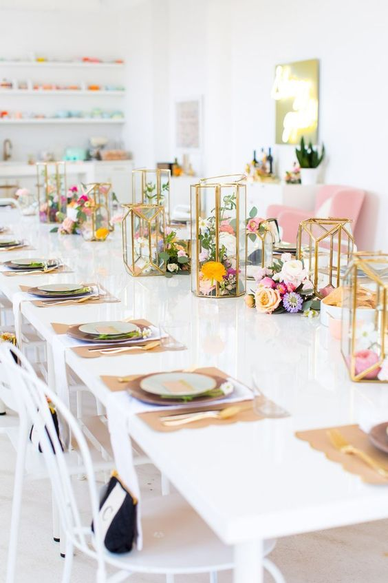 an indoor garden bridal shower table with bright blooms, gilded candle lanterns, burlap placemats and gold cutlery