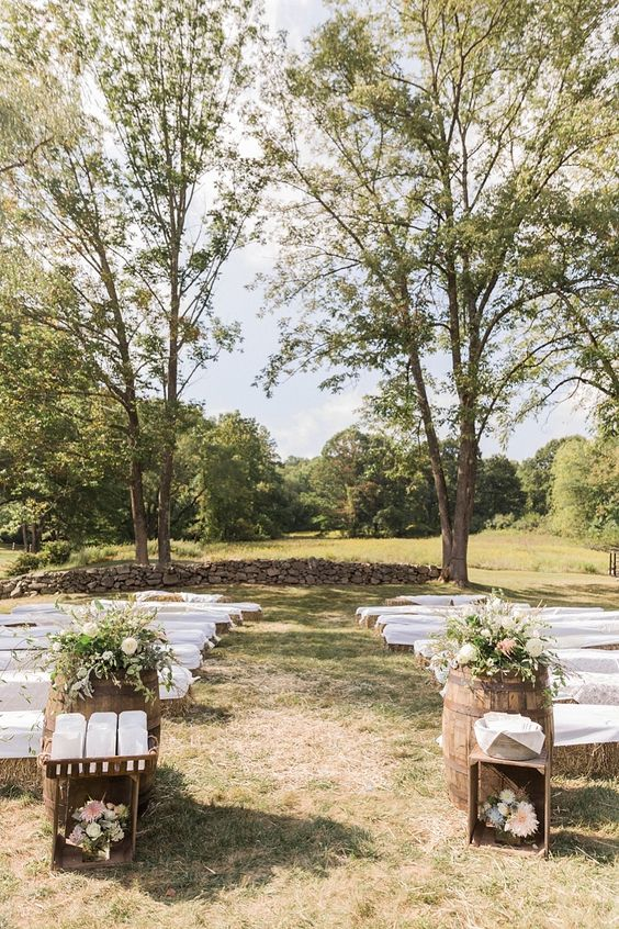 an outdoor barn wedding ceremony space with benches of hay, barrels with greeneyr and blooms and baskets
