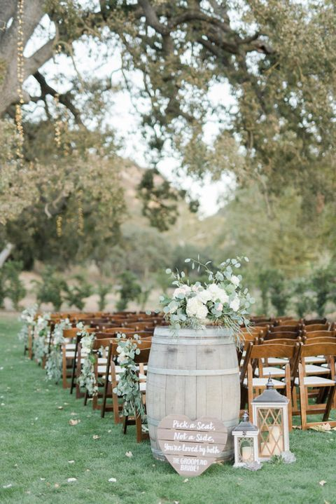 an outdoor barn wedding ceremony space with stained chairs, elegant eucalyptus and bloom arrangements, candle lanterns and string lights