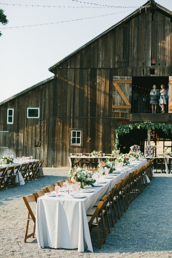 an outdoor barn wedding reception space with long tables, neutral linens, pink florals and greenery and stained chairs