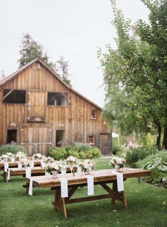 an outdoor barn wedding reception space with long tables, white linens, neutral and pink floral arrangements is a cool idea